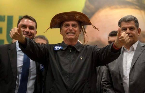Flávio Bolsonaro, Jair Bolsonaro e Gustavo Bebianno em evento de campanha. (Crédito da foto: Mauro Pimentel / AFP)
