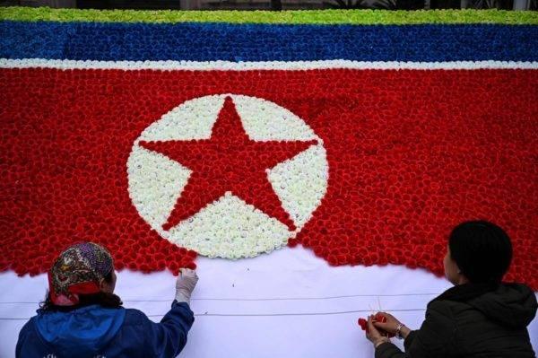 Trabalhadores montam uma bandeira nortecoreana com flores de papel em uma rua de Hanói, Vietnã, em preparação ao encontro entre Donald Trump e Kim Jong-un nesta semana. Foto: Jewel SAMAD / AFP
