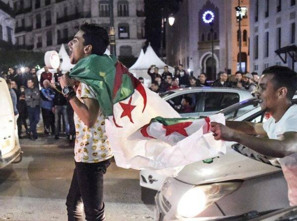 Manifestantes argelinos comemoram após o presidente Abdelaziz Bouteflika anunciar a retirada da sua candidatura a um quinto mandato. Foto: Ryad Kramdi / AFP
