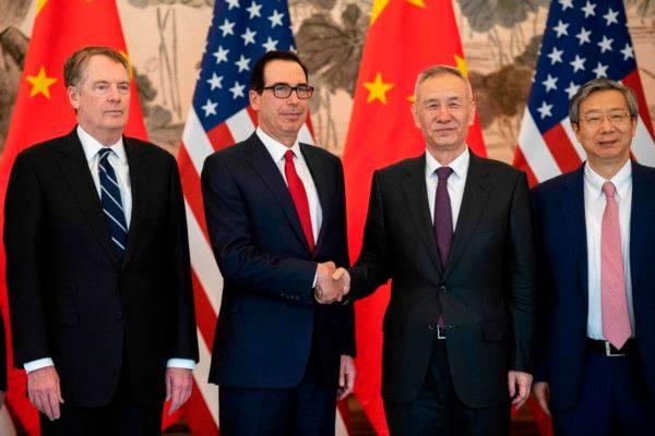O vice-primeiro-ministro da China, Liu He, aperta a mão do secretário do Tesouro americano, Steven Mnuchin. Os dois estão acompanhados do diretor do banco da China, Yi Gang, e o representante para o comércio dos EUA, Robert Lighthizer (Foto: Nicolas Asfouri/ Pool/ AFP)