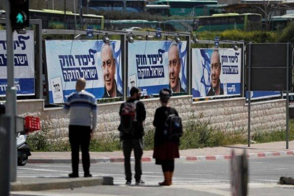 Israelenses passam por outdoors da campanha eleitoral do primeiro-ministro de Israel, Benjamin Netanyahu, em Jerusalém, em 3 de abril de 2019 | Foto: HOMAS COEX/AFP