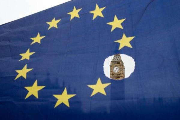 Nesta foto de março de 2017, um manifestante contrário ao Brexit segura uma bandeira da União Europeia com uma das estrelas simbolicamente recortada em frente ao Palácio de Westminster, em Londres. Foto: Oli Scarff / AFP