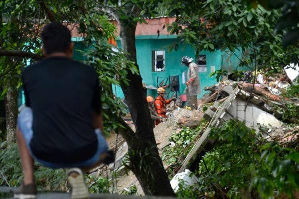 Bombeiros trabalham no Morro da Babilônia, no Leme, zona sul da cidade,  para resgatar o corpo de um homem que está soterrado devido ao deslizamento provocado pelo temporal que atingiu a cidade do Rio de Janeiro