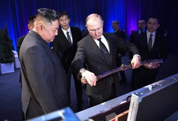 O presidente russo Vladimir Putin observa uma espada que ganhou de presente do ditador da Coreia do Norte, Kim Jong-un, no primeiro encontro entre os dois. Foto: Alexey NIKOLSKY / SPUTNIK / AFP