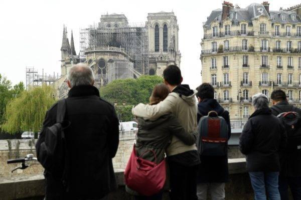 Pessoas observam os estragos em Notre-Dame de Paris, após o incêndio. Bertrand Guay/AFP
